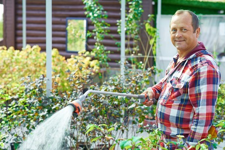 Mature gardener looking at camera with smile while watering plants in the garden photo