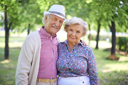 Couple of senior man and woman looking at camera in the park at summer photo
