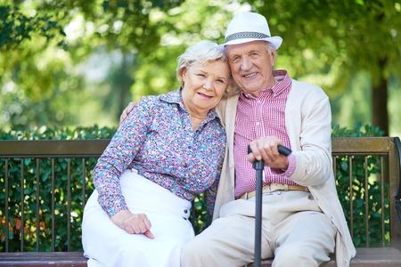 Gelukkig senioren zittend op een bankje in het park en genieten van rust Stockfoto
