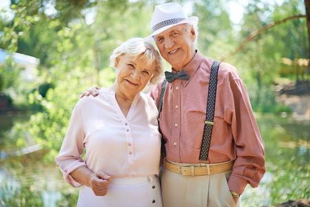 Szczęśliwego seniorów w smart casual korzystających letniego wypoczynku