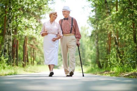 Happy seniors taking a walk in the park on sunny day Stockfoto