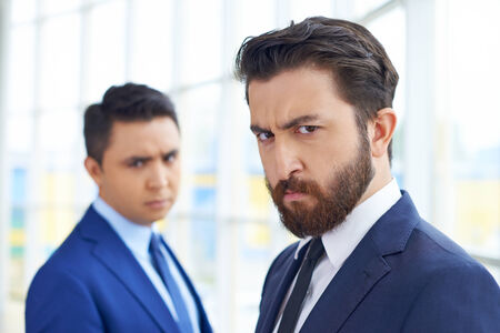 Frowning businessman looking at camera on background of his displeased colleague