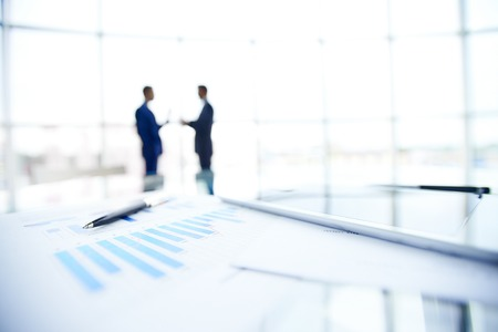Business documents and pen at workplace on background of businessmen interacting photo