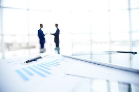 documents d'affaires et un stylo au lieu de travail sur fond d'hommes d'affaires interaction