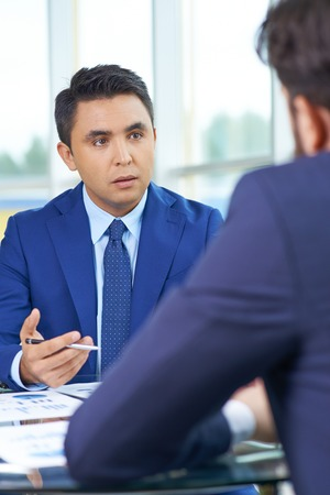 Elegant businessman communicating with his colleague at meeting