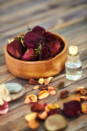 Dry roses, their petals and aromatic oils on wooden surface
