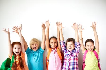 Extatische vrienden met opgeheven armen kijken naar de camera Stockfoto