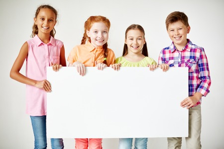 primary education: Friendly classmates with blank paper looking at camera with smiles