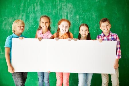 Vriendelijke klasgenoten met blanco papier