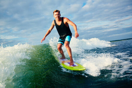 Male surfer riding on waves photo