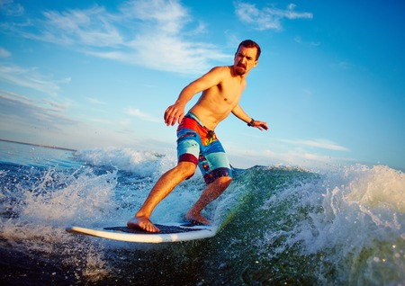 Young man surfboarding in summer photo