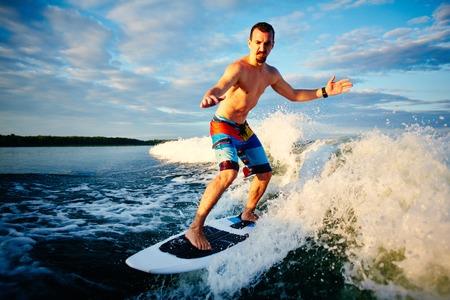 niño sin camisa: Activo joven pasar del ocio del hombre de surf en las olas