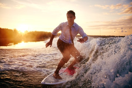 Young man in wet clothes surfboarding at summer resort photo