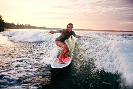 夏のリゾート地で若い女性 surfboarding
