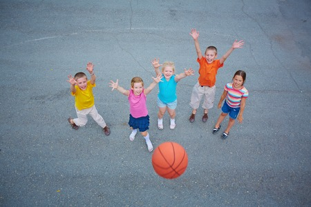 Cute friends playing basketball on sports ground