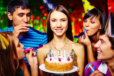 happy occasion: Portrait of joyful girl with birthday cake looking at camera at party with her friends near by