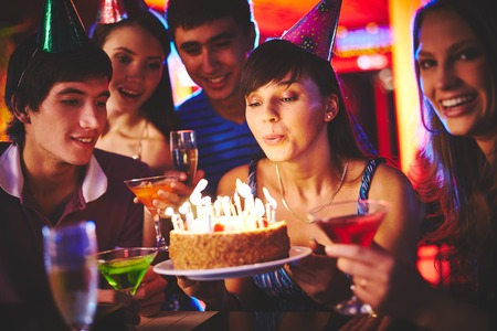 Pretty girl blowing on candles on birthday cake at party photo