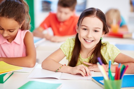 kids studying: Happy little girl looking at camera at lesson with her friend near by