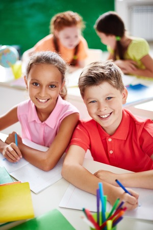 Two schoolkids looking at camera while drawing on background of little girls Stock Photo