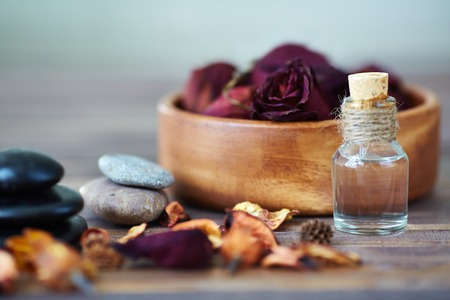 Dry roses in bowl, spa stones and aromatic oil photo