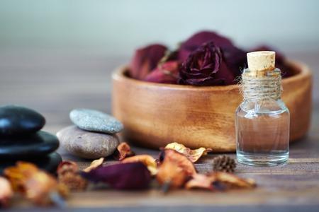 destilacion: Rosas secas en un tazón, spa de piedras y aceite aromático Foto de archivo