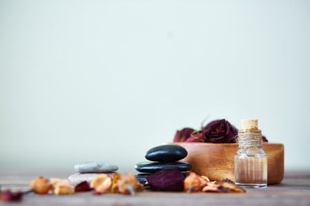 destilacion: Rosas secas en un tazón, spa de piedras y esencias aromáticas en botella