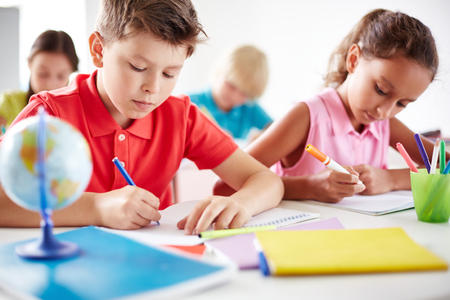 bambini pensierosi: Allievi Junior disegno con evidenziatori multi-colore a lezione Archivio Fotografico
