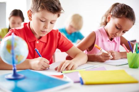 ni�os con l�pices: Alumnos junior dibujo con rotuladores de varios colores en la lecci�n