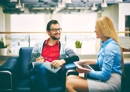 corporate meeting: Smiling businessman discussing plans or ideas with his secretary in office