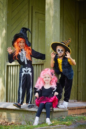 antichrist: Group of Halloween girls posing on the porch of dilapidated house