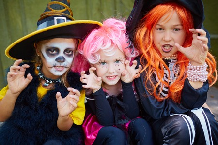 portrait of three little girls in halloween costumes looking at camera with frightening gesture stock photo