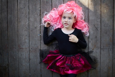 Portrait of happy Halloween girl in pink wig looking at camera Stock Photo