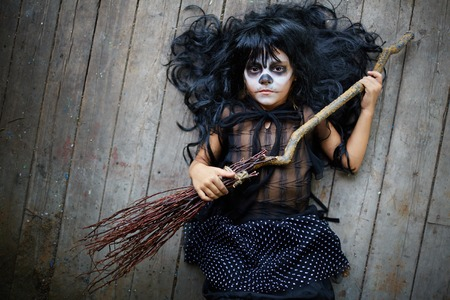 antichrist: Portrait of cute Halloween girl with broom looking at camera