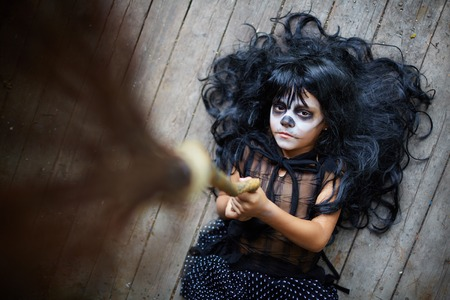 sulky: Portrait of eerie girl with broom looking at camera with sulky expression Stock Photo