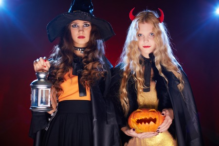 Two girls with lantern and pumpkin looking at camera photo