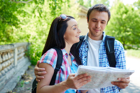 where to go: Modern travelers with map discussing where to go