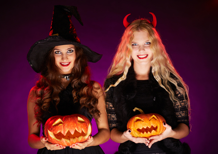 Happy witches with pumpkins looking at camera photo