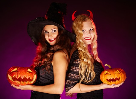 Two happy females with jack-o-lanterns looking at camera with smiles photo