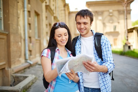 Couple of travelers studying map of ancient town during their journey photo