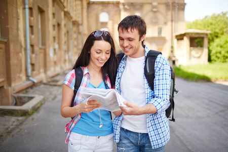 Couple of happy young travelers discussing map of ancient town during their journey photo