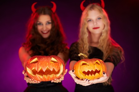 antichrist: Two carved Halloween pumpkins held by females