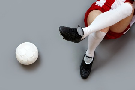 Sports player legs with soccer ball near by photo