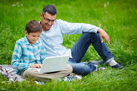 Young man and his son networking outdoors photo