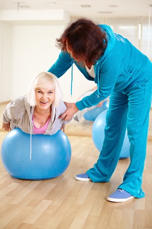 vertical wellness: Happy woman doing physical exercise with fitness ball in sport gym