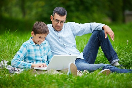 Young man and his son using laptop while relaxing in the park photo
