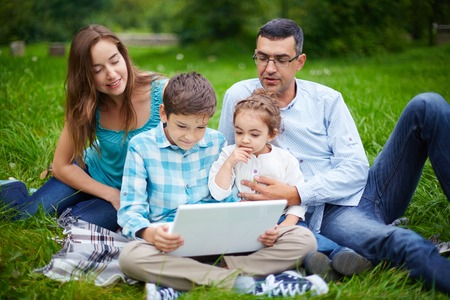 Modern family of four using laptop while resting in park photo