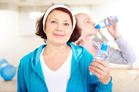 Happy aged woman with plastic bottle of water on background of other female drinking photo