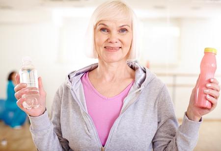 damas antiguas: Mujer madura feliz con botellas de plástico de agua y yogur mirando a la cámara