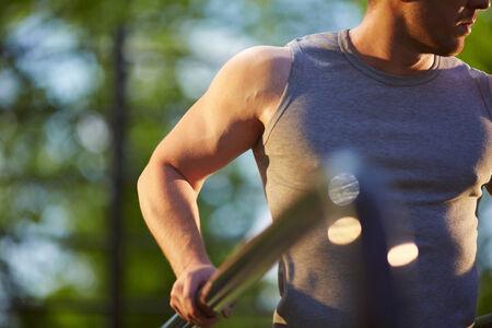 activewear: Sportsman in grey vest training on sport equipment outside