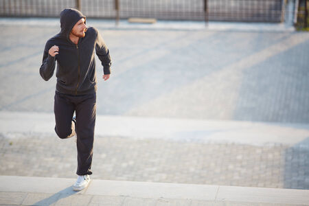 activewear: Portrait of young man in activewear jogging outside